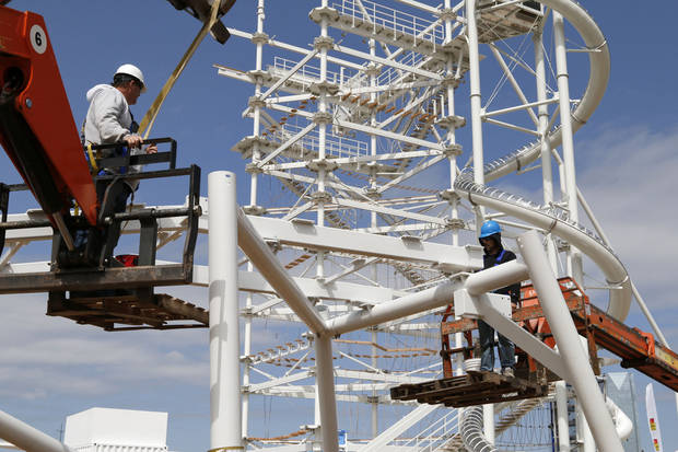 photo -                    Workers assemble components of the landing area for the Sky Zip, a 700-foot zip line designed to take people from top of SandRidge Sky Trail (seen in the background) across the Oklahoma River and back again.                                        Photo by Paul Hellstern, The Oklahoman