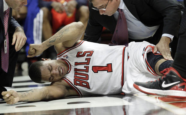 photo - Chicago Bulls guard Derrick Rose (1) reacts after an injury during the fourth quarter of  Game 1 in the first round of the NBA basketball playoffs against the Philadelphia 76ers in Chicago, Saturday, April 28, 2012. The Bulls won 103-91. (AP Photo/Nam Y. Huh) ORG XMIT: CXA107