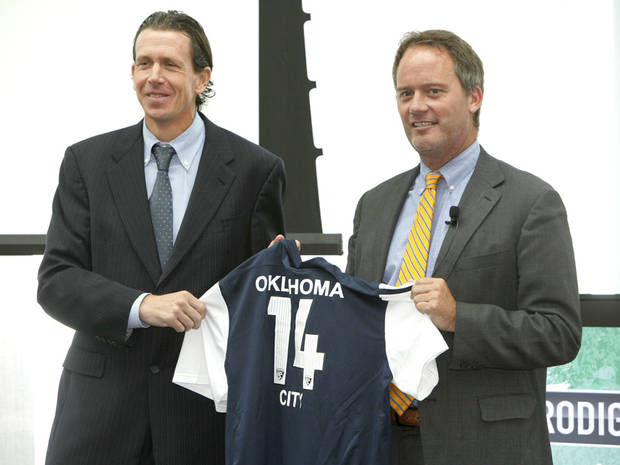 photo - United Soccer Leagues President Tim Holt, left, and John Allgood, Prodigal's Executive Vice President of Sales and Marketing, hold a symbolic soccer jersey during a press conference at the Devon Tower in Oklahoma City, OK, Tuesday, July 2, 2013,  Photo by Paul Hellstern, The Oklahoman
