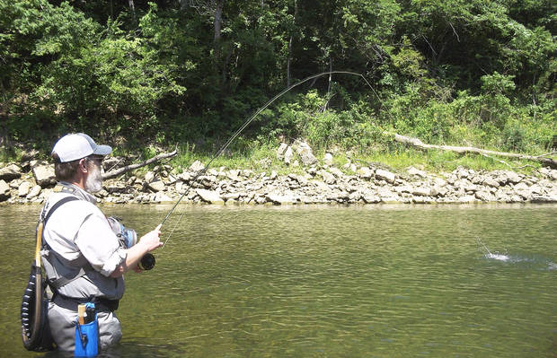 photo - Fly fisherman Jim Sinclair hooks a rainbow trout on the White River below the Beaver Lake dam near Eureka Springs, Ark. PHOTO BY ED GODFREY, THE OKLAHOMAN