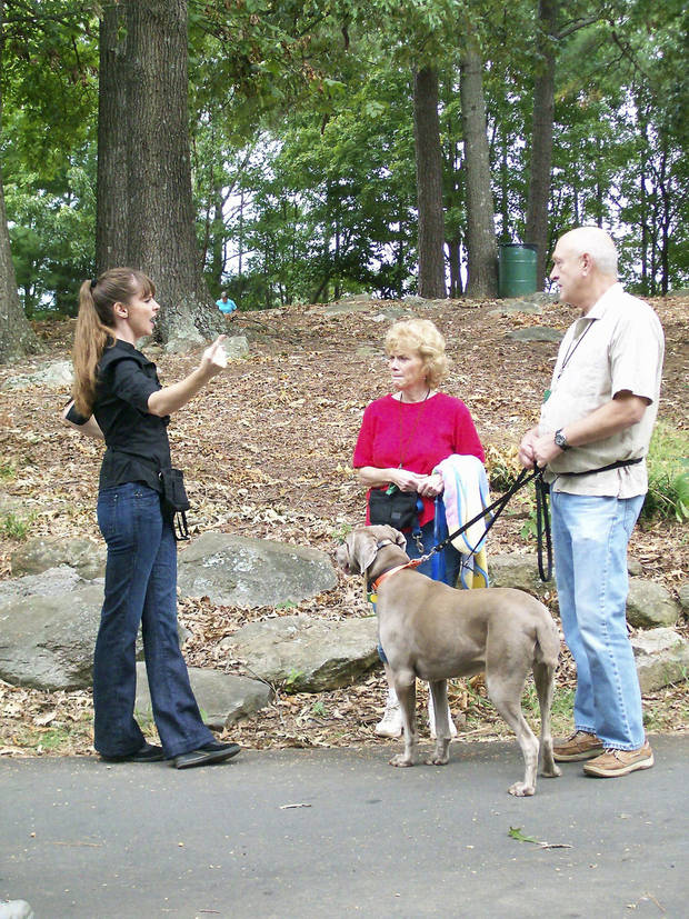 photo - Victoria Stilwell, left, works on dog leash training with Debbie and Todd Rodgers and their dog, Yaphit, a Weimaraner.AP/ANIMAL PLANET PHOTO