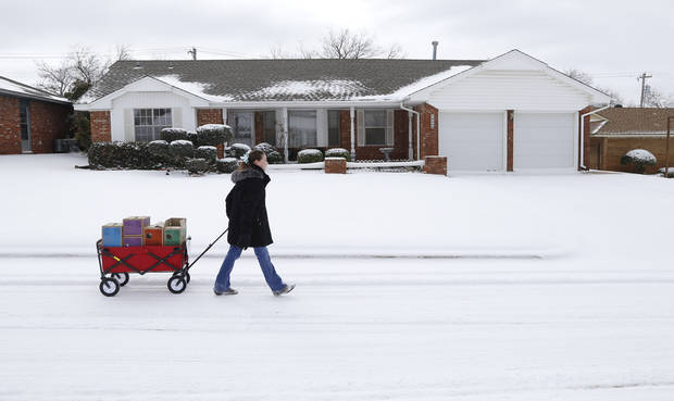 photo - Girl Scout Katie Francis pulls her wagon full of boxes of cookies in the snow through a neighborhood in Warr Acres sellling cookies Thursday, February 6, 2014. Photo by Doug Hoke, The Oklahoman