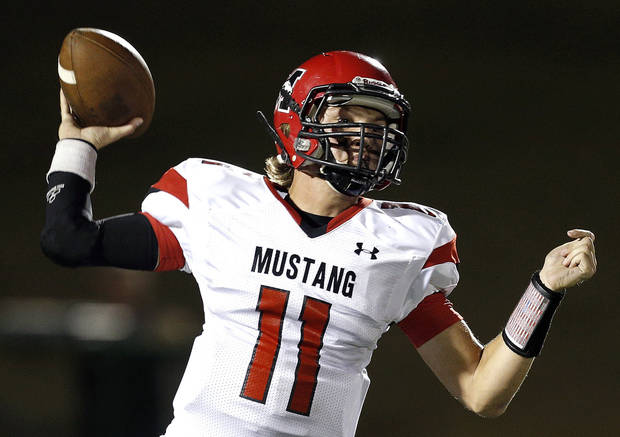 photo - Mustang's Chandler Garrett throws a pass during the high school football game between Edmond Santa Fe and Mustang at Wantland Stadium in Edmond, Okla.,   Thursday, Oct. 3, 2013. Photo by Sarah Phipps, The Oklahoman