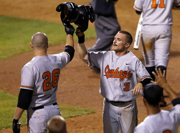photo - Oklahoma State's Saulyer Saxon (3) celebrates with Zach Fish (26) after scoring against Kansas in the fifth inning of a Big 12 Baseball Championship tournament game at the Chickasaw Bricktown Ballpark in Oklahoma City, Friday, May, 24, 2013. Photo by Bryan Terry, The Oklahoman