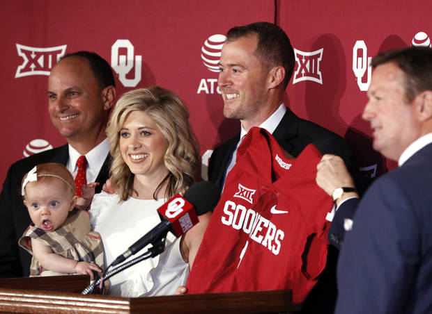 Lincoln Riley holds up a jersey after he is announced as new head football coach at the University of Oklahoma. From left are: Athletic Director Joe Castiglione, Riley's wife, Caitlin, daughter Stella and to his right is Bob Stoops. [Photo by Steve Sisney, The Oklahoman]
