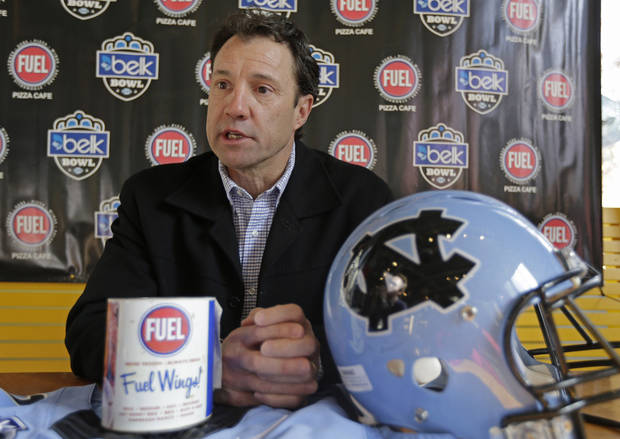 photo - North Carolina coach Larry Fedora answer a question during the media day event for the Belk Bowl NCAA college football game in Charlotte, N.C., Friday, Dec. 27, 2013. North Carolina faces Cincinnati in the Belk Bowl on Saturday. (AP Photo/Chuck Burton)