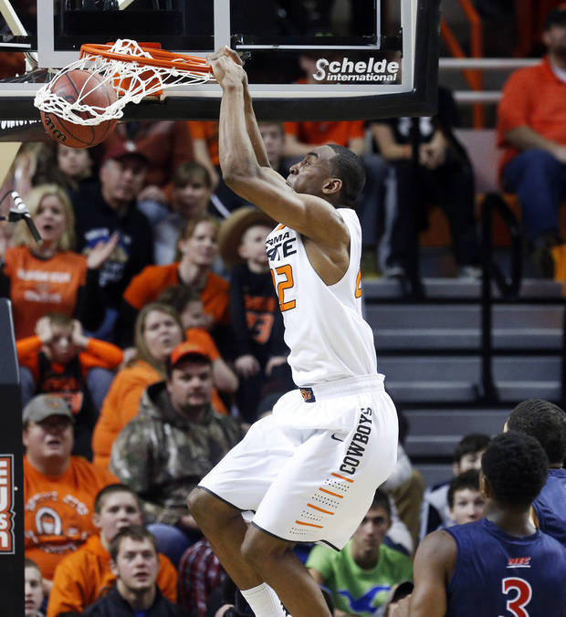 photo - Oklahoma State wing Markel Brown dunks in front of Robert Morris guard Kavon Stewart (3) in the first half of an NCAA college basketball game in Stillwater, Okla., Monday, Dec. 30, 2013. (AP Photo/Sue Ogrocki)