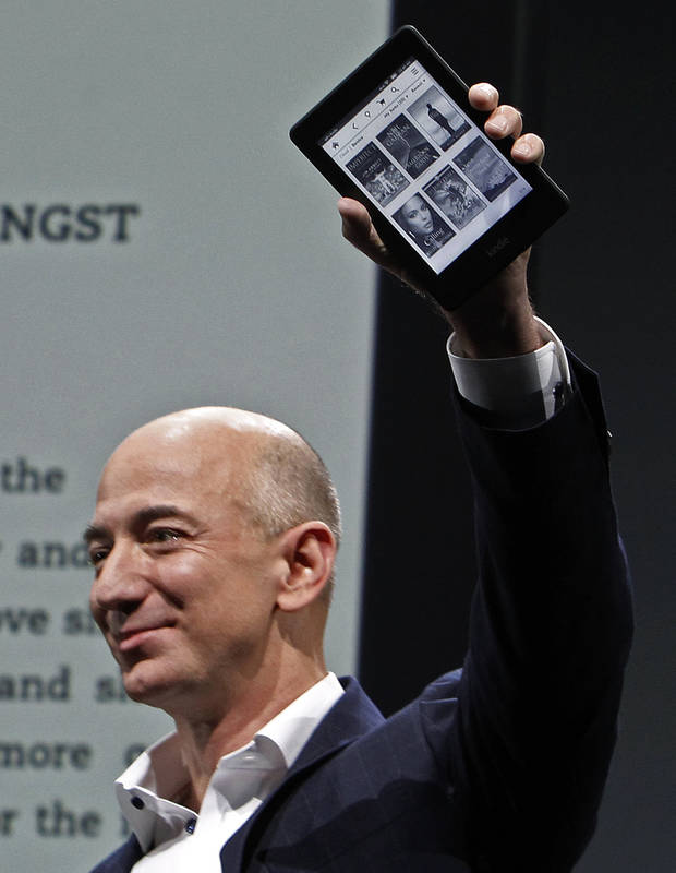 Jeff Bezos, CEO and founder of Amazon, holds the Kindle Paperwhite at the introduction of the new Amazon Kindle Fire HD and Paperwhite devices in Santa Monica, Calif., Thursday, Sept. 6, 2012. (AP Photo/Reed Saxon) ORG XMIT: CARS101