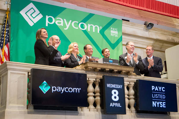 photo -                    Paycom Software executives applaud during Wednesday morning's opening bell ceremony at the New York Stock Exchange. Those attending included Chief Operating Officer Stacey Pezold; Chief Finanical Officer Craig Boelte; founding member Shannon Rowe; CEO Chad Richison; Chief Information Officer William Kerber; John Merrell, a vice president with the stock exchange; and Chief Sales Officer Jeff York.                     Photo provided