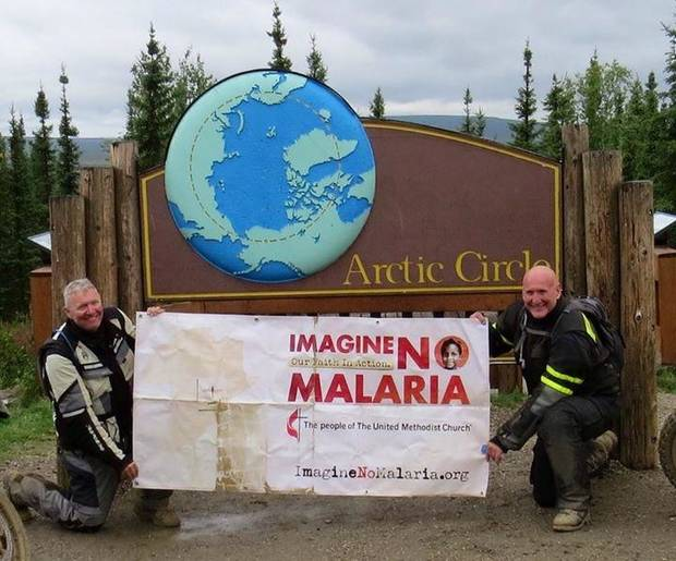 "The Rev. Randy Shrauner, executive pastor at United Methodist Church of the Servant in Oklahoma City, at right, raises a ""Imagine No Malaria"" banner at the Arctic Circle along with the Rev. Dennis Miller of Ohio."