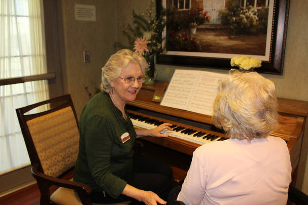 Maddie Seward, Concordia Life Plan Community's memory care lifestyle coordinator, engages with a resident at the piano. [PROVIDED]
