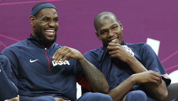 photo - Team USA's LeBron James, left, jokes with teammate Kevin Durant as they sit on the bench against Tunisia during a men's basketball game at the 2012 Summer Olympics, Tuesday, July 31, 2012, in London. (AP Photo/Charles Krupa) <strong>Charles Krupa</strong>
