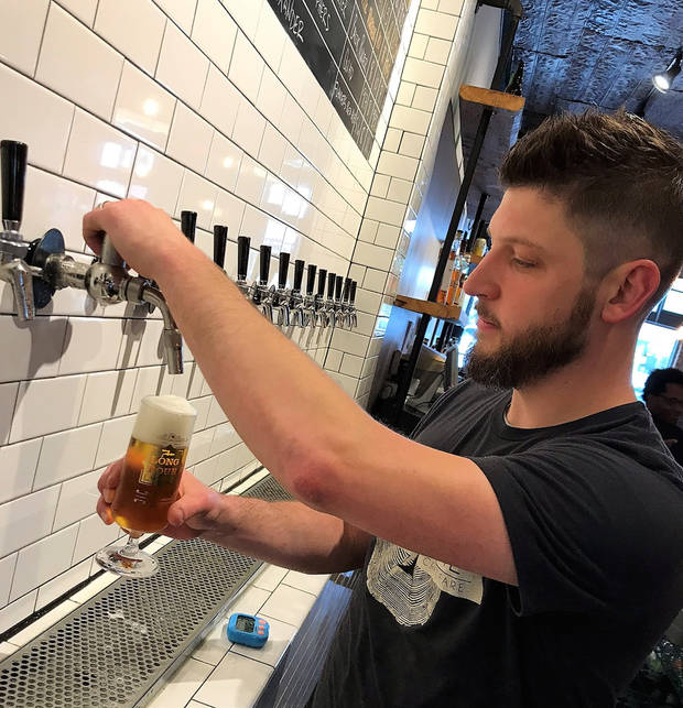 Oak & Ore owner Micah Andrews pours a pilsner the old-fashioned way. [Dave Cathey/The Oklahoman]