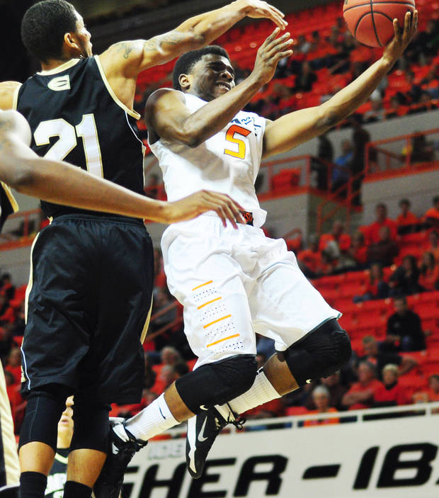 photo - OSU freshman guard Stevie Clark jumps around a defender to score in an exhibition against Emporia State. Photo by KT King, for the Oklahoman