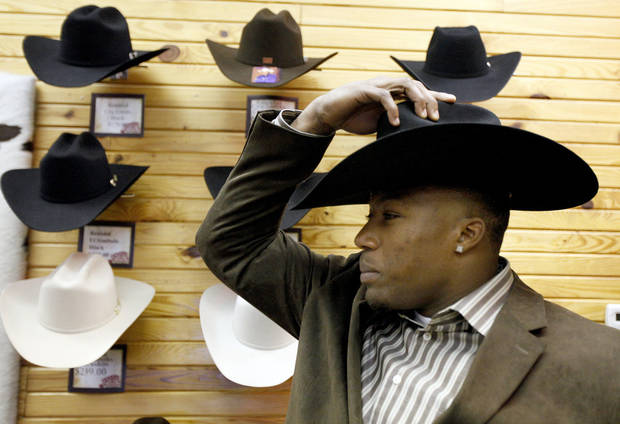 photo - University of Tennessee defensive back and 2009 Jim Thorpe Award Winner  Eric Berry tries on cowboy hats at Tener's Western Outfitters on Sunday. Photo by Sarah Phipps, The Oklahoman