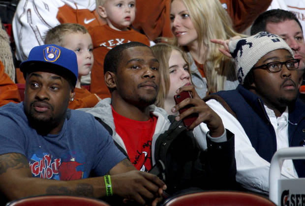 photo - Thunder forward Kevin Durant, center, watches a basketball game between OU and Texas with his friend Randy Williams, left, and brother, Tony Durant, right. Photo by Bryan Terry, The Oklahoman
