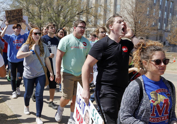 People, including teachers, students and parents from Moore Public Schools, march on the south side of the state Capitol on the 11th day of a walkout by Oklahoma teachers in Oklahoma City, Thursday, April 12, 2018. The Moore superintendent opened schools and ended the district's participation in the walkout on Thursday. Photo by Nate Billings, The Oklahoman