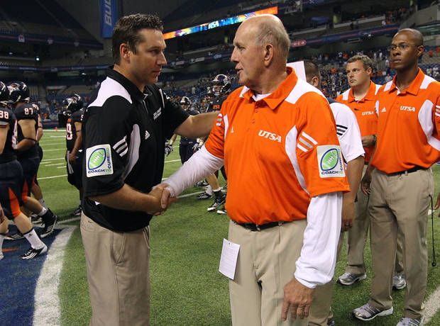 photo - UTSA head coach Larry Coker (right) shakes hands with Bacone&#039;s Trevor Rubly at the end of their game at the Alamodome on Saturday, Sept. 24, 2011. UTSA defeated Bacone, 54-7.
