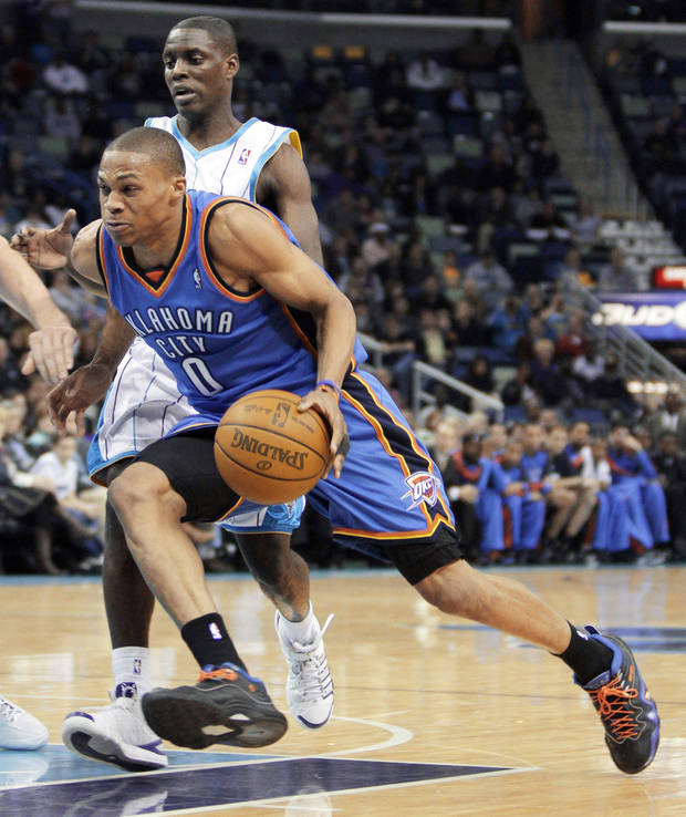 photo - OKC's Russell Westbrook (0) drives past Hornets  guard Darren Collison during  Wednesday's game. AP photo