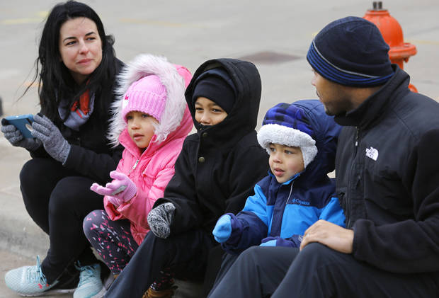 Jerald, right, and Hailey, left, Harrison sit on the curb with their children, Ava, 5, Jayden, 7, and Jayce, 4, while trying to keep warm in sub-freezing temperatures as they watch the Martin Luther King, Jr. Day parade in Oklahoma City on Monday, Jan. 15, 2018. Photo by Jim Beckel, The Oklahoman
