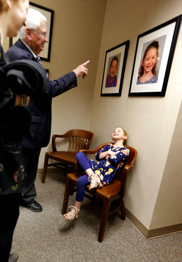 Mayor David Holt's daughter Maggie, 6, sat under her photograph in the mayor's conference room at City Hall on Tuesday. Her father has substituted portraits of Oklahoma City children for photos of former mayors that previously adorned the conference room's wall. Mayors' photos were moved to a different wall in the suite that includes the city manager's and mayor's offices. [Photo by Steve Sisney, The Oklahoman]