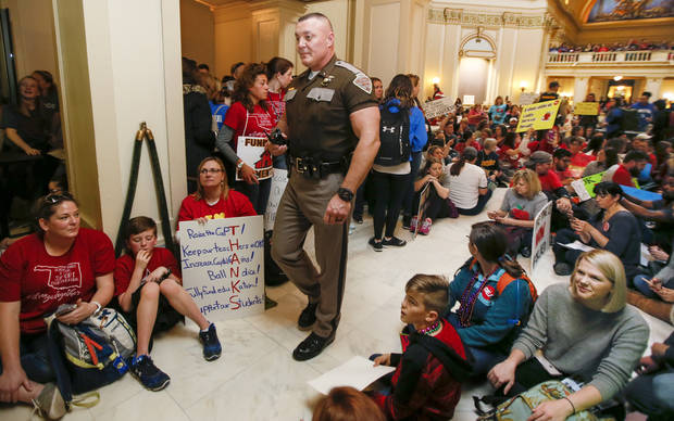 A state trooper walks by teachers and their supporters as they sit on the fourth floor in front of the entrance to the House of Representatives during the second day of a walkout by Oklahoma teachers at the state Capitol in Oklahoma City, Tuesday, April 3, 2018. Photo by Nate Billings, The Oklahoman