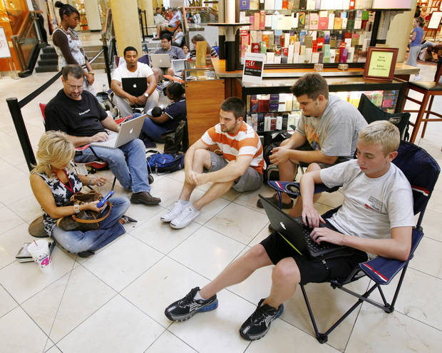 Clockwise from lower left, Vicki Baldini, Darrell Solomon, Ronald Henderson, Jamila Henderson, holding 8-week-old Ronald Henderson Jr., Jason Stulce, Brandon Jackson, Corbin Jackson and others wait in line to buy the iPhone at the Apple Store in Penn Square Mall in Oklahoma City, Friday, June 29, 2007. The line outside Penn Square Mall began forming at 3:30 a.m. Baldini is the first person in the line. [THE OKLAHOMAN ARCHIVES]