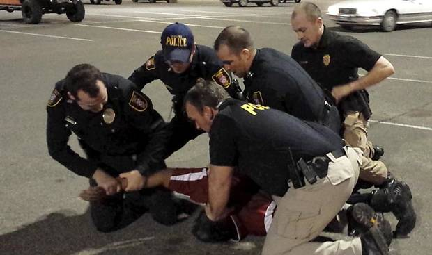 photo - Left: This cellphone video screen capture shows Moore police officers restraining Luis Rodriguez in the parking lot at the Warren Theatre on Feb. 15. Rodriguez died after the incident and the state medical examiner's office Wednesday announced that Rodriguez's death is classified as a homicide.