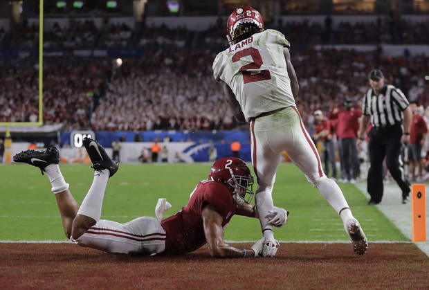 Oklahoma wide receiver CeeDee Lamb (2) scores a touchdown as Alabama defensive back Patrick Surtain II (2) grabs his leg, during the second half of the Orange Bowl NCAA college football game, Saturday, Dec. 29, 2018, in Miami Gardens, Fla. (AP Photo/Lynne Sladky)