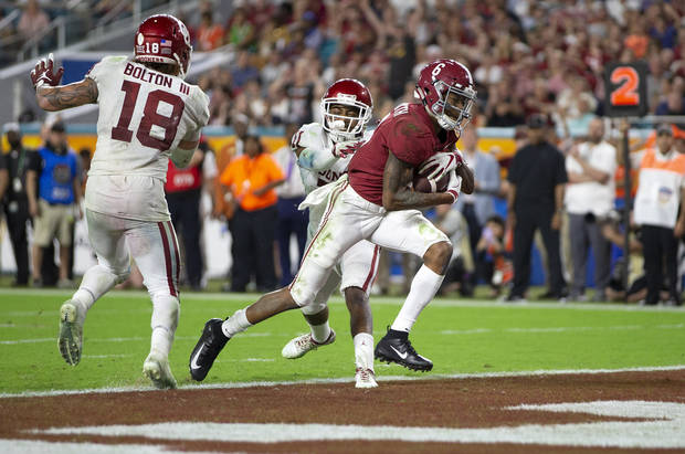 Alabama receiver DeVonta Smith (6) crosses the goal line between Sooners linebacker Curtis Bolton (18) and Parnell Motley in Orange Bowl last season. (Palm Beach Post)