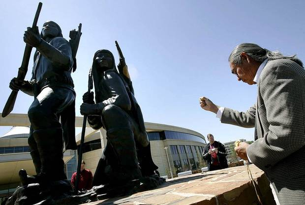 "Phillip Houser uses ceremonial pollen, or medicine, to bless artwork created by his father Allan Houser during the unveiling and dedication of the bronze statue, titled ""Unconquered,"" outside the Oklahoma History Center in Oklahoma City Wednesday April 26, 2006. [The Oklahoman Archives]"