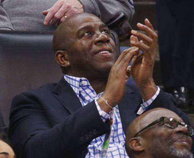 Magic Johnson, president of basketball operations for the Los Angeles Lakers, applauds as he watches the kiss cam on the scoreboard during the third quarter of an NBA basketball game between the Lakers and the Oklahoma City Thunder in Oklahoma City, Friday, Feb. 24, 2017. Oklahoma City won 110-93. (AP Photo/Sue Ogrocki)