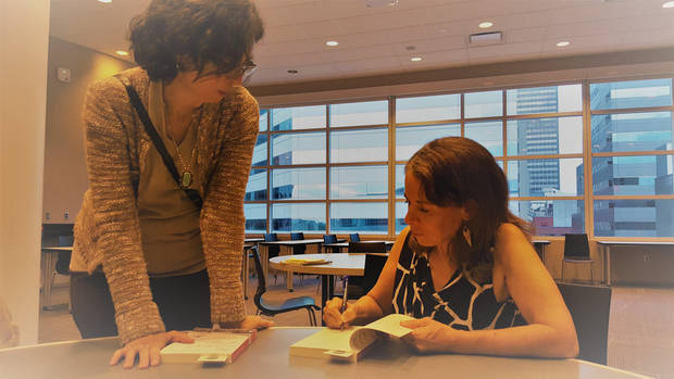 "Author Jo Ivester signs a copy of her book ""The Outskirts of Hope"" for Fatima Abrantes of Oklahoma City at the Downtown Library in Oklahoma City. [Photo by Carla Hinton, The Oklahoman]"