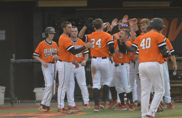 photo -                    OSU's Connor Costello (24) and his teammates celebrate his two-run home run in the sixth inning Sunday at Allie P. Reynolds Stadium.                     Photo by JACKIE DOBSON, Tulsa World