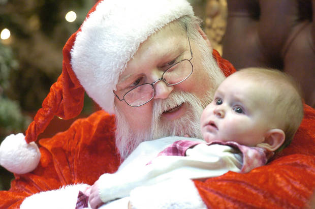 photo - Oklahoma City, Thursday, 12/22/05.   Working Santas, Santas that have a regular job but choose to play Santa Claus simply for the love of it. Roger Kreke has been playing Santa for years. His beard is natural too. Kreke holds Jayden Greenway, 5, OKC, for her first photo with Santa at Northpark Mall.   Staff photo by David McDaniel. ORG XMIT: KOD