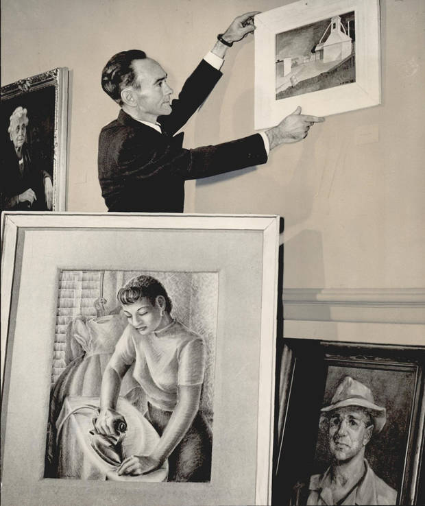 Oliver Rearick, a curator at the Oklahoma Art Center in Oklahoma City's Municipal Auditorium (now the Civic Center Music Hall) hangs the first of 200 paintings selected for display in the Association of Oklahoma Artists exhibit on Oct. 26, 1948. [The Oklahoman Archives]
