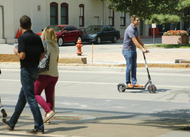 A Bird scooter, here headed north on Robinson Avenue, was among the rentals distributed around downtown earlier this month. The electric scooters are activated using a smartphone app. [Photo by Doug Hoke,The Oklahoman]