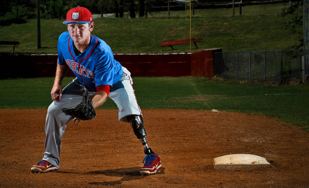photo - Binger-Oney High School senior first baseman DeKota Green poses for a photo at first base showing his prosthetic leg on Monday, May 5, 2014 in Binger, Okla.  Green had to have his left leg removed after an ATV accident.      Photo by Chris Landsberger, The Oklahoman