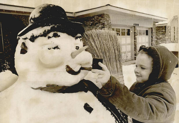 "Jan. 20, 1966: Snowmen of all sizes and shapes sprang up in Oklahoma. This one, which bears a resemblance to the legendary ""Frosty,"" is viewed by Dale Pierce, 5. [Photo by Don Brown, The Oklahoman Archives]"