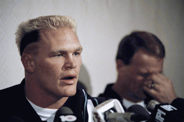 photo - With head coach Barry Switzer of the Oklahoma Sooners, right, reacting unhappily in the background, All-American linebacker Brian Bosworth speaks to the press about his being barred from playing in the 53rd Annual Orange Bowl Classic New Years Day, Friday, Dec. 26, 1986, Miami Beach, Fla. Bosworth was barred because steroids were found in his system but he said he deserves a right to give my body the ultimate challenge and be as healthy as I can be. (AP Photo/Judy Sloan)
