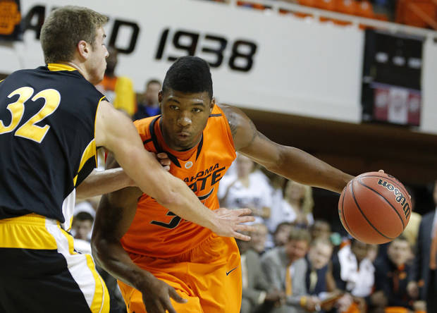 photo - Oklahoma State's Marcus Smart tries to get around Ottawa's Stephen Feighny during the college basketball game between Oklahoma State University and Ottawa (Kan.) at Gallagher-Iba Arena in Stillwater, Okla., Thursday, Nov. 1, 2012. Photo by Sarah Phipps, The Oklahoman