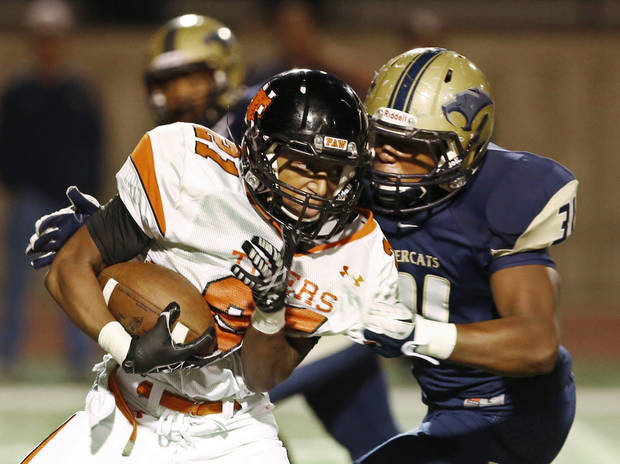 photo - Norman's Imond Robinson is tackled by Southmoore's Terrance Bonner during the first half in Moore, Friday  October 12, 2012. Photo By Steve Gooch, The Oklahoman