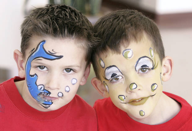 photo - Seth Baratz, 7, left, and Zachary Wright, 5, got their faces painted Saturday during a Mended Little Hearts Christmas Party. Photo by Steve Gooch,The Oklahoman
