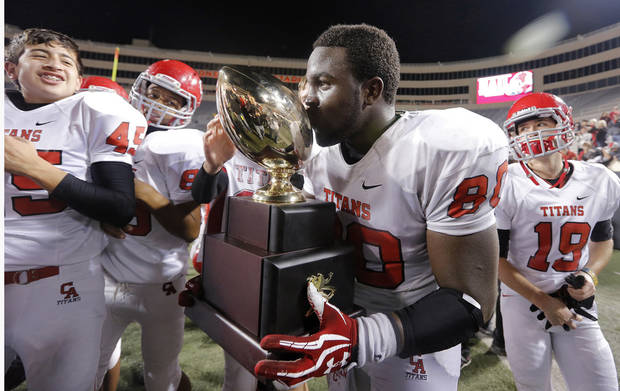photo - CLASS 5A HIGH SCHOOL FOOTBALL STATE CHAMPIONSHIP GAME / CELEBRATE / CELEBRATION: Carl Albert's Chantz Woodberry (80) kisses the trophy while celebrating the win over East Central during the Class 5A Oklahoma state championship football game between Carl Albert High School and Tulsa East Central High School at Boone Pickens Stadium on Saturday, Dec. 1, 2012, in Stillwater, Okla.   Photo by Chris Landsberger, The Oklahoman