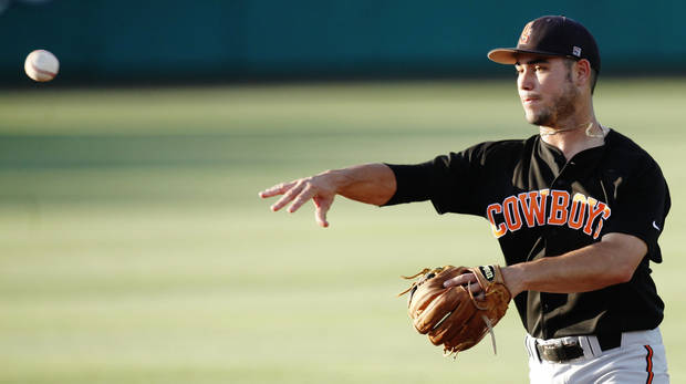 photo - Oklahoma State second baseman Tim Arakawa (2) throws to first base during an NCAA Regional Baseball game between the Oklahoma State and Cal State Fullerton at Allie P. Reynolds stadium in Stillwater on May 31, 2014. Photo by KT King/The Oklahoman