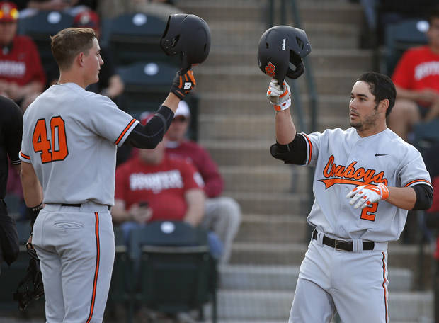 photo - OSU's Tim Arakawa, right, celebrates with Craig McConaughy after hitting a home run during the Bedlam baseball game between the University of Oklahoma and Oklahoma State University at L. Dale Mitchell Park in Norman, Okla., Tuesday, April 1, 2014. Oklahoma State won 3-1. Photo by Bryan Terry, The Oklahoman