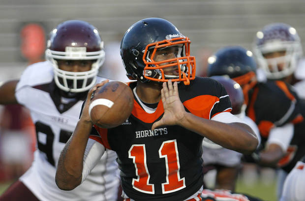 photo - HIGH SCHOOL FOOTBALL: Booker T. Washington quarterback prospect Dominique Alexander passes under pressure from the Jenks defense during a scrimmage at Booker T. Washington High School in Tulsa on Friday, August 19, 2011. MATT BARNARD/Tulsa World ORG XMIT: DTI1108192049350475