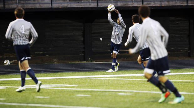 photo - Edmond North's Zac Medawattage (14) throws the ball in to a teammate during a high school soccer game between Edmond North and Midwest City in Midwest City on Tuesday, April 29, 2014. Edmond North defeated Midwest City 10-0.  Photo by KT King, The Oklahoman