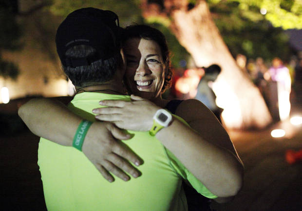 photo - Amy Downs, a survivor of the blast, hugs her husband Terry Head near the survivor tree before the start the 14th Annual Oklahoma City Memorial Marathon in Oklahoma City, Sunday, April 27, 2014. Downs is running her fourth marathon after volunteering the other previous runs, and her husband is running his first half marathon. Photo by KT King/The Oklahoman
