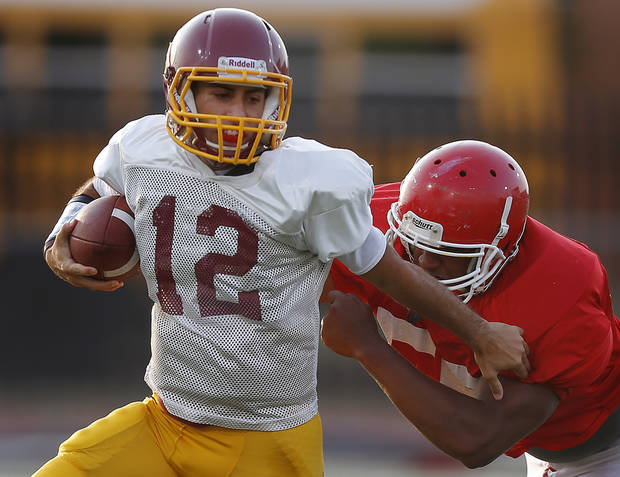 photo - HIGH SCHOOL FOOTBALL: Putnam City North's John Simon fights off Lawton's BJ Scott during a football scrimmage at Putnam City High School in Warr Acres, Okla., Thursday, August 16, 2012. Photo by Bryan Terry, The Oklahoman